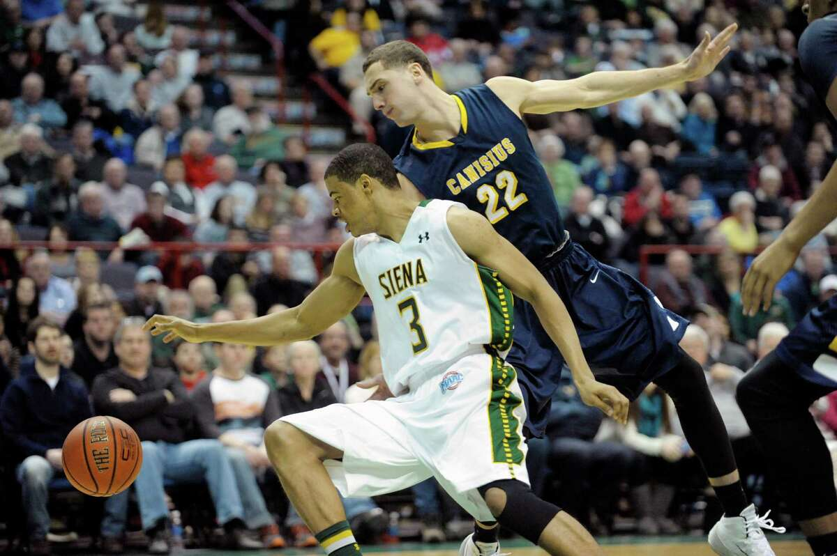 Ryan Oliver, left, of Siena turns back to retrieve the ball after losing control of it during the Siena and Canisius mena€™s basketball game at the Times Union Center on Sunday, Feb. 16, 2014 in Albany, NY. (Paul Buckowski / Times Union)