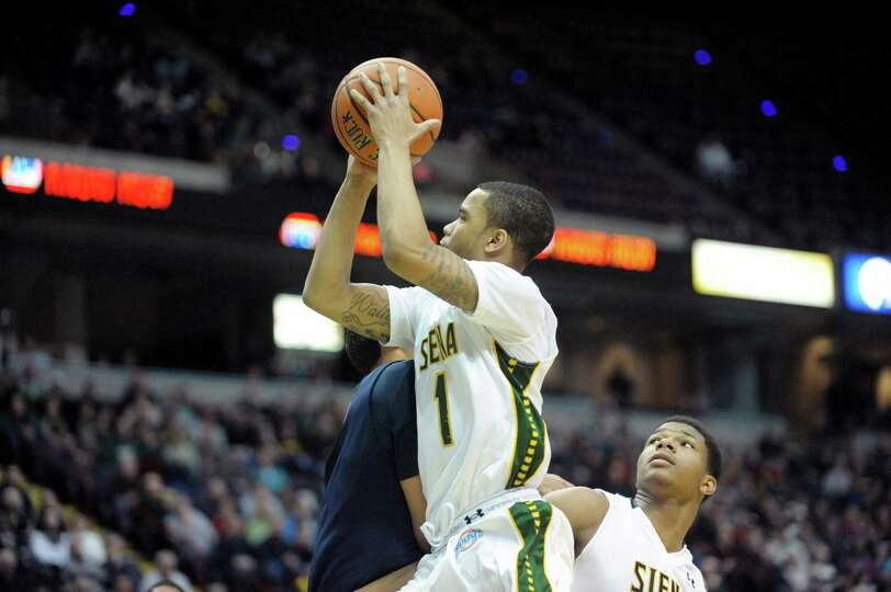 Marquis Wright of Siena drives to the basket and puts up a shot during the Siena and Canisius mena€