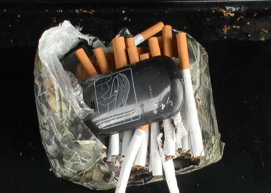 A Florida Department of Corrections photo shows a cellphone and cigarettes found in a package. Photo: Associated Press / Florida Department of Correction