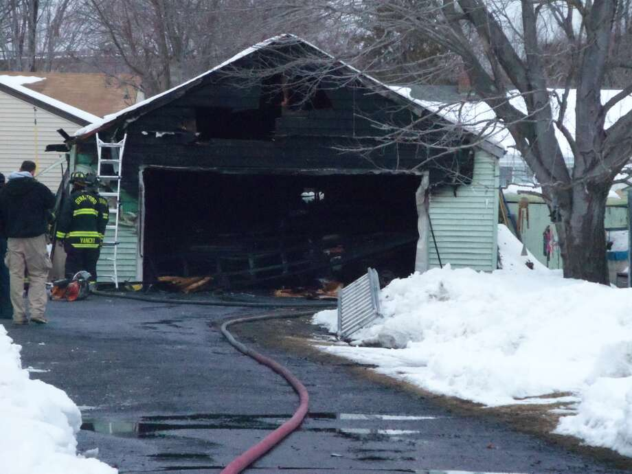 A garage and the two vehicles parked inside were destroyed after one of the cars caught fire Sunday, Feb. 16, 2014, in Stratford.