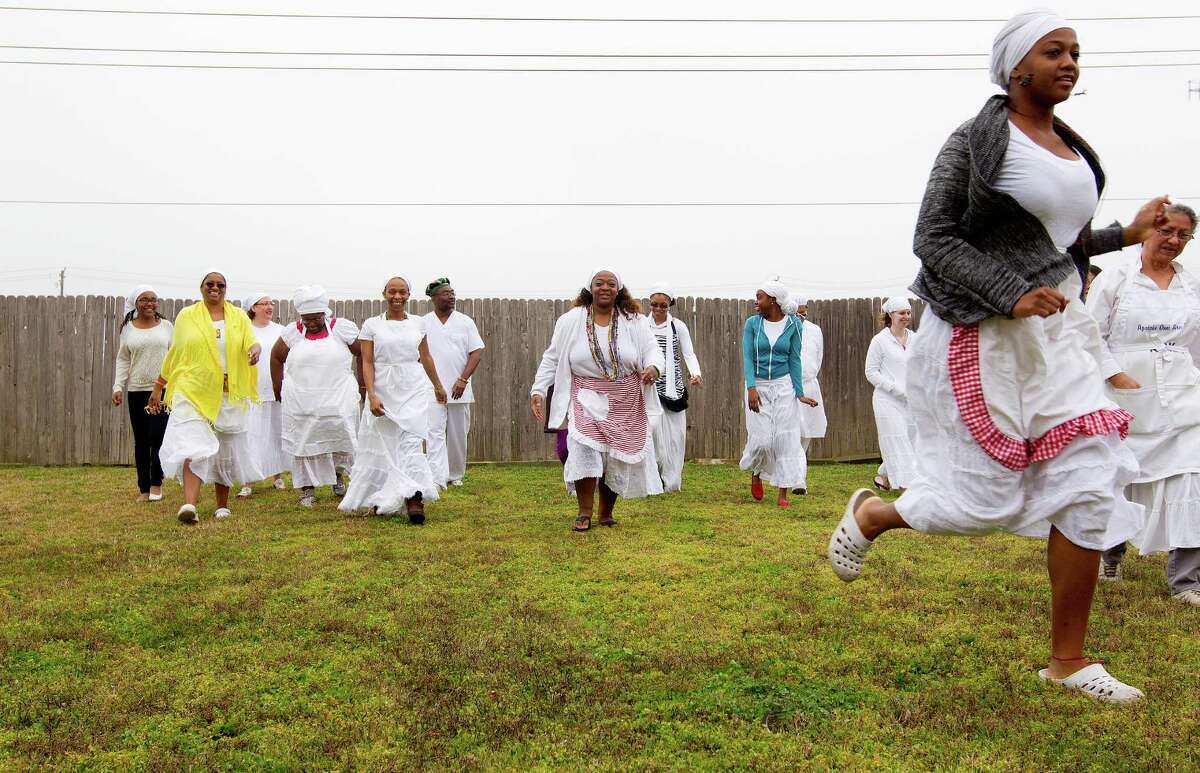 Santeria worshipers move from the yard into the home of Faizah Perry to cook, clean and prepare for another ceremony after an eggun, or ancestral, ceremony.