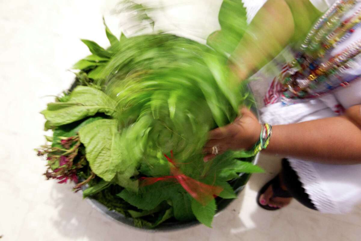 Faizah Perry puts together greens for a ceremony honoring Osain, the orisha of nature, who rules over forests, herbalism and healing.