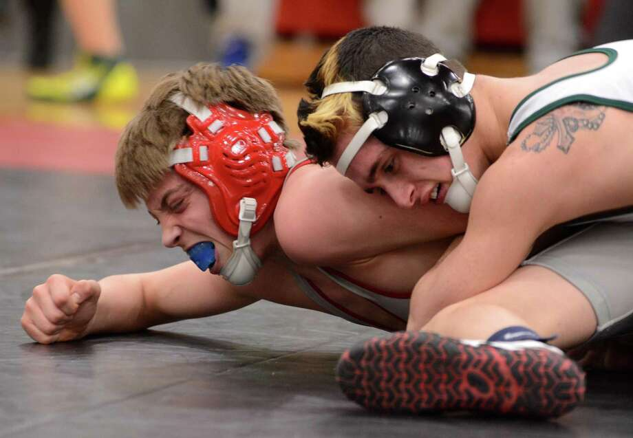 New Fairfield High Schools Alec Opsal, left, and New Milfords Halim Bougeli wrestle for the SWC championship in the 106 weight class on Sunday Feb. 16, 2104 at Pomperaug High School. Photo: Lisa Weir / The News-Times Freelance