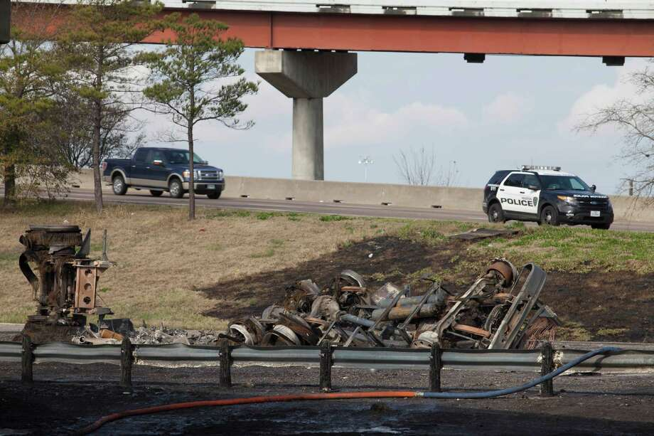 Houston police and fire crews  investigate an 18- wheeler crash in Houston that left the vehicle a skeleton and at least one person dead on Sunday. The accident happened near the Gulf Freeway and eastbound section of the South Loop. Photo: Eric Kayne / Eric Kayne