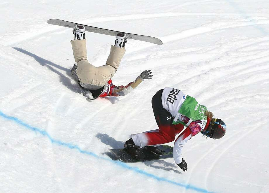 Lindsey Jacobellis falls while leading her snowboardcross semifinal as Canada's Dominique Maltais tries to avoid her. Photo: Sergei Grits, Associated Press