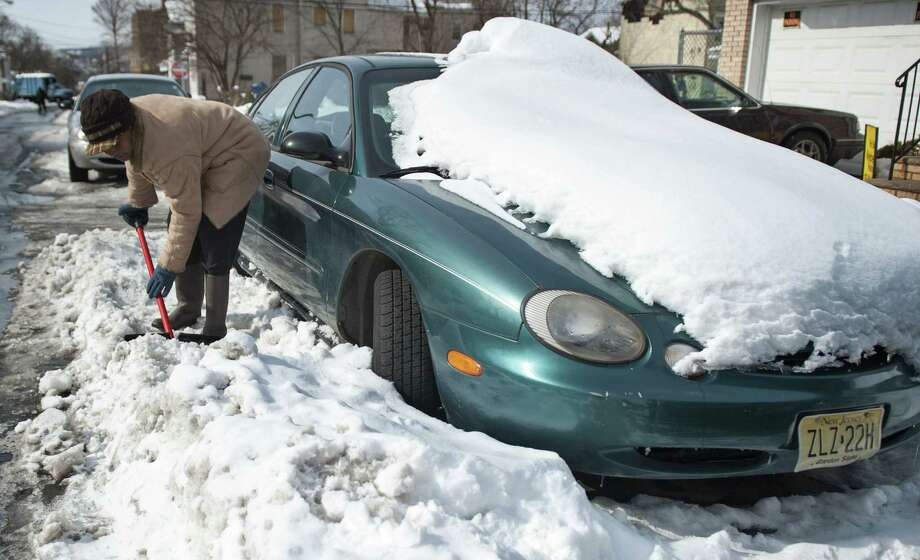 Ingrid Parham works to remove frozen snow surrounding her car in Paterson, N.J. Other areas in the Northeast saw heavy accumulations of snow and high winds from a weekend snowstorm. Photo: Amy Newman / Northjersey.com / Northjersey.com