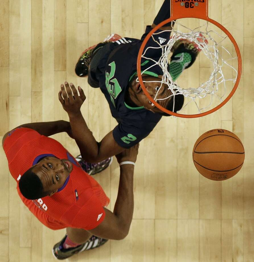 Dwight Howard, of the Rockets (12) and John Wall, of the Wizards (2) vie for a loose ball. Photo: Gerald Herbert, Associated Press