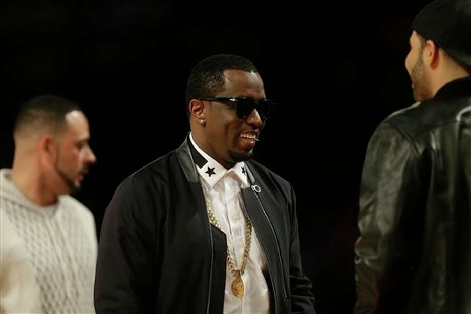 Rapper P Diddy greets fans during the NBA All Star basketball game, Sunday, Feb. 16, 2014, in New Orleans. (AP Photo/Gerald Herbert) Photo: Gerald Herbert, AP / AP