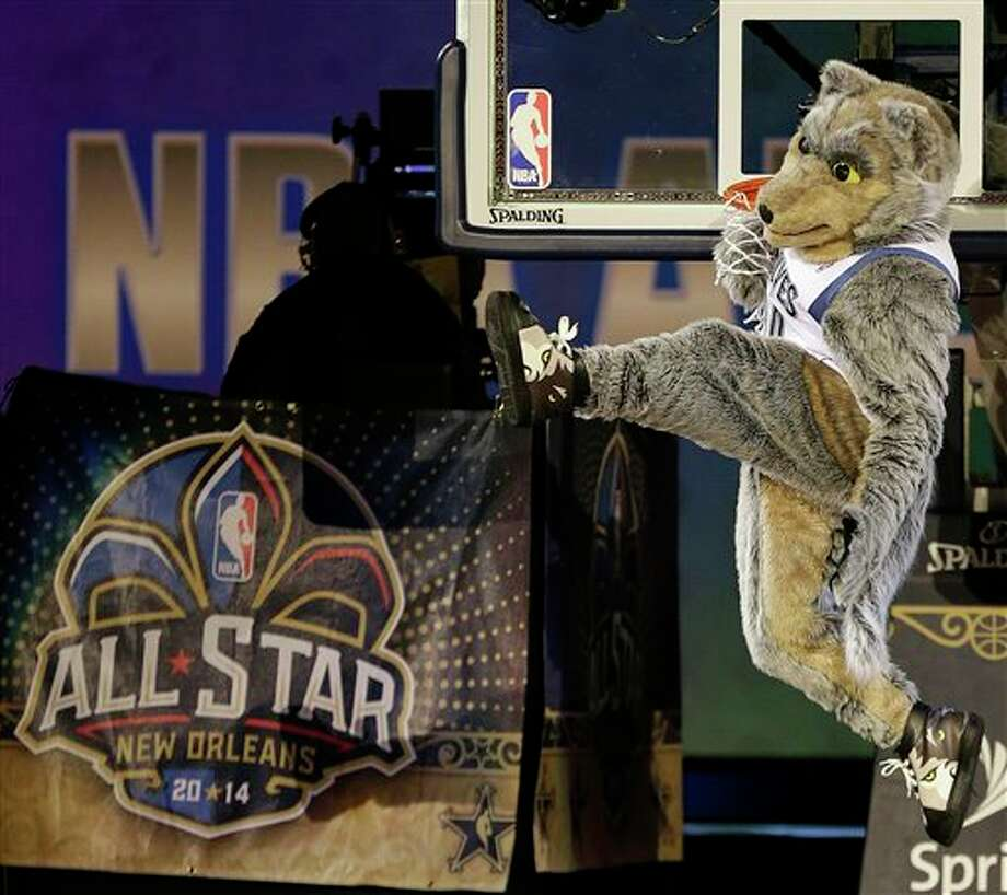 The Minnesota Timberwolves mascot hangs from the rim after getting his hand stuck after a dunk before the NBA All Star basketball game, Sunday, Feb. 16, 2014, in New Orleans. (AP Photo/Gerald Herbert) Photo: Gerald Herbert, AP / AP