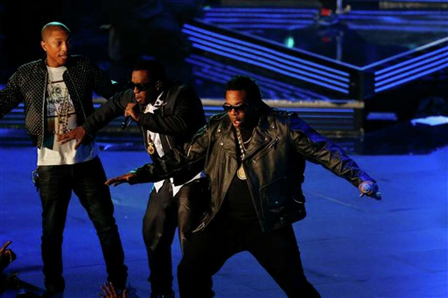 Rappers P Diddy, center, Pharrell Williams, left, and Busta Rhymes perform during the NBA All Star basketball game, Sunday, Feb. 16, 2014, in New Orleans (AP Photo/Bill Haber) Photo: Bill Haber, AP / FR170136 AP