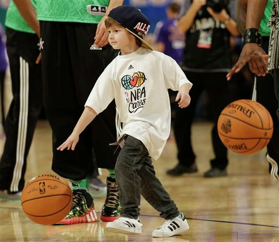 A child dribbles the ball before the NBA All Star basketball game, Sunday, Feb. 16, 2014, in New Orleans. (AP Photo/Gerald Herbert) Photo: Gerald Herbert, AP / AP