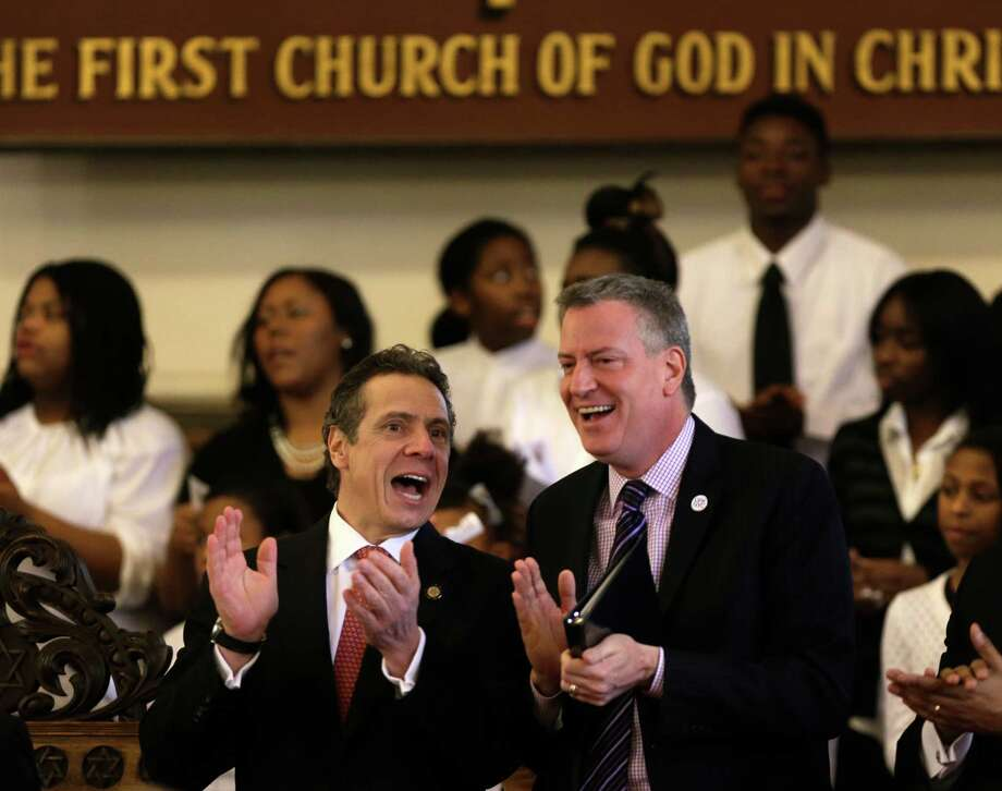 New York Gov. Andrew Cuomo, left, and New York City Mayor Bill de Blasio clap along with the choir during a Black, Puerto Rican, Hispanic and Asian Legislative Caucus Weekend church service at the Wilborn Temple on Sunday, Feb. 16, 2014, in Albany, N.Y. (AP Photo/Mike Groll) ORG XMIT: NYMG102 Photo: Mike Groll / AP
