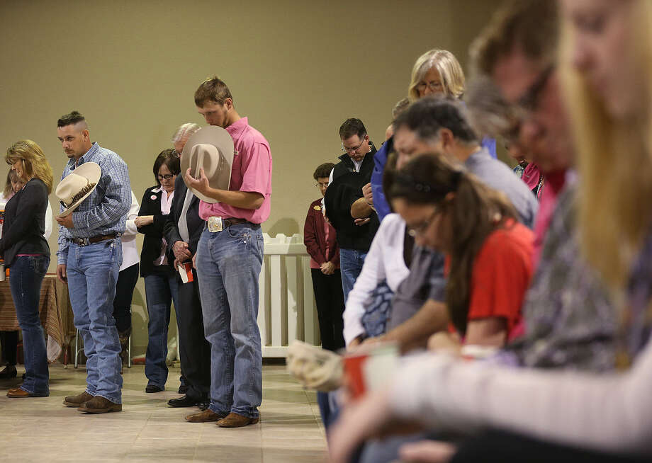 Wesley Walters (in blue) and Jared Maddox (in pink) remove their hats during prayer at the San Antonio Stock Show & Rodeo Cowboy Church services on Sunday. The Cowboy Church will be held at 9 a.m. next Sunday. Photo: Photos By Jerry Lara / San Antonio Express-News / © 2014 San Antonio Express-News