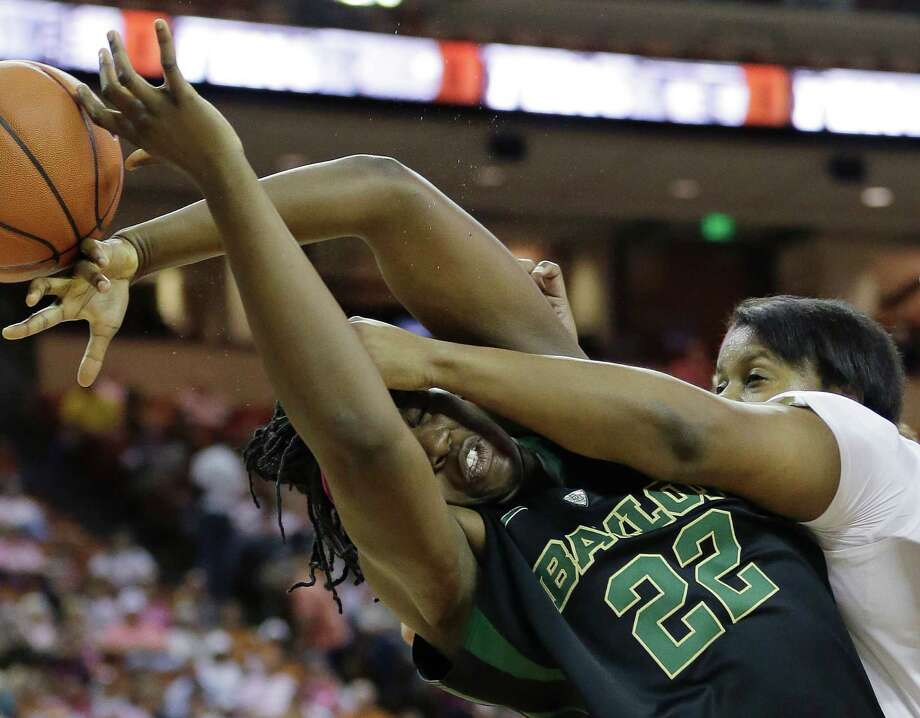 Baylor's Sune Agbuke (22) gets the worst of a rebounding battle with Texas' Nekia Jones. Photo: Eric Gay, STF / AP