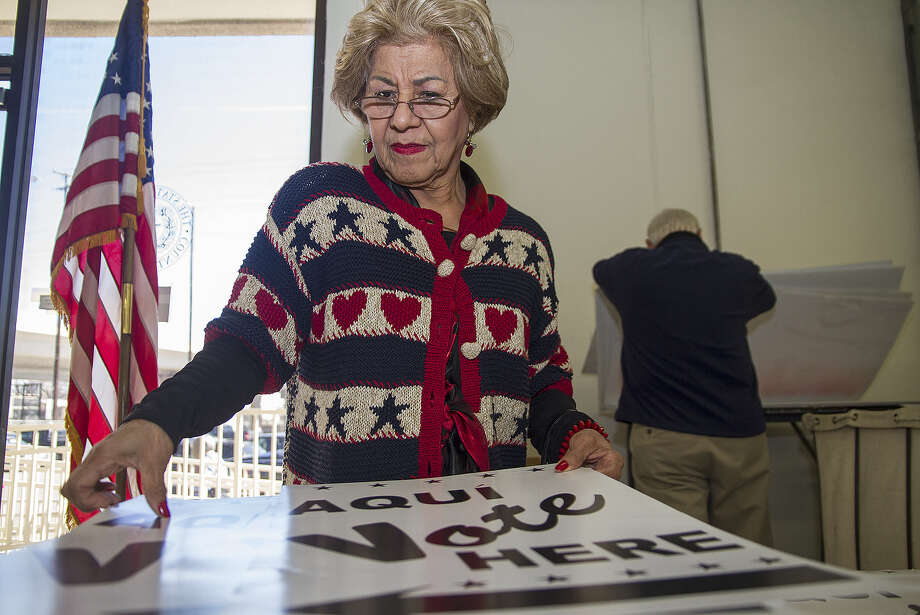 Evelyn R. Parra, an alternate election judge for early voting at the Las Palmas Library voting site, picks up signs at the Bexar County Elections Department's warehouse last week. Photo: Alma E. Hernandez / For The San Antonio Express-News