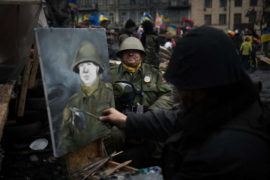 Big man on canvas:An artist paints the portrait of an anti-government protester in full regalia on a barricade in Kiev. Photo: Martin Bureau, AFP/Getty Images