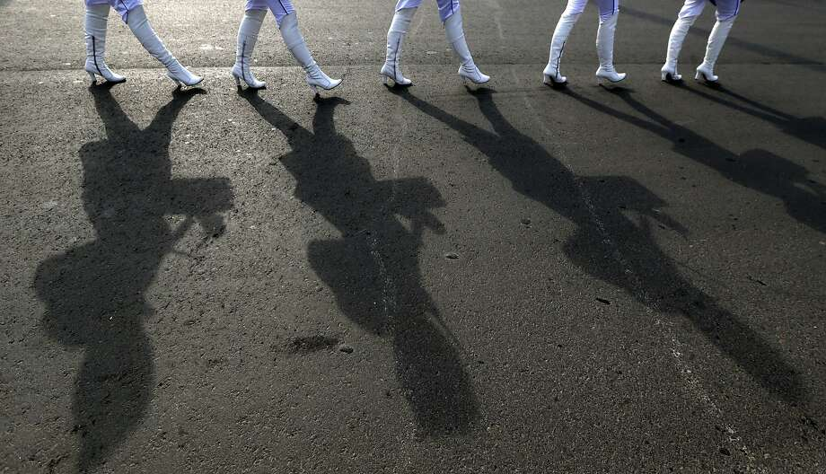 Female drummers cast shadows on the ground as they march near medals plaza in Olympic Park at the 2014 Winter Olympics, Monday, Feb. 17, 2014, in Sochi, Russia. Photo: Julio Cortez, Associated Press
