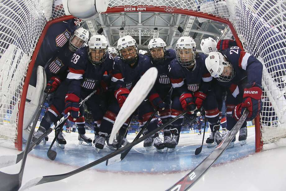 Members of Team USA pack into the opening of the net for a photograph before the first period of the 2014 Winter Olympics women's semifinal ice hockey game against Sweden at Shayba Arena, Monday, Feb. 17, 2014, in Sochi, Russia. (AP Photo/Bruce Bennett, Pool) Photo: Bruce Bennett, Associated Press