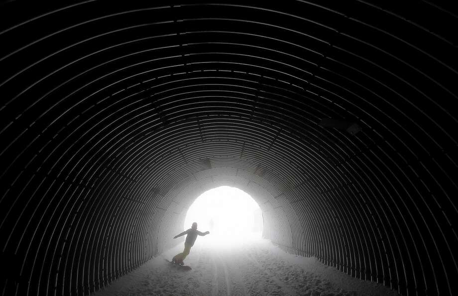 A snowboarder goes through a tunnel near the alpine skiing training slopes at the Sochi 2014 Winter Olympics, Monday, Feb. 17, 2014, in Krasnaya Polyana, Russia. Photo: Christophe Ena, Associated Press