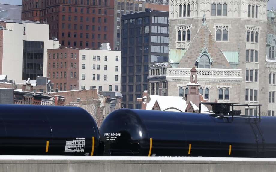 Railroad oil tanker cars are parked along Interstate 787 in downtown Albany, N.Y., on Friday, Feb. 7, 2014. The Port of Albany has become a hub for the U.S. oil business, taking shipments from North Dakota's Bakken Shale daily by mile-long trains and shipping it in tankers down the Hudson River to refineries. Opponents of a proposal to build boilers to liquefy heavy crude passing through Albany by rail are drawing attention to the capital's emergence as a major hub for the transport of oil that's widely considered risky from an environmental and safety standpoint.  (AP Photo/Mike Groll) Photo: Mike Groll, AP