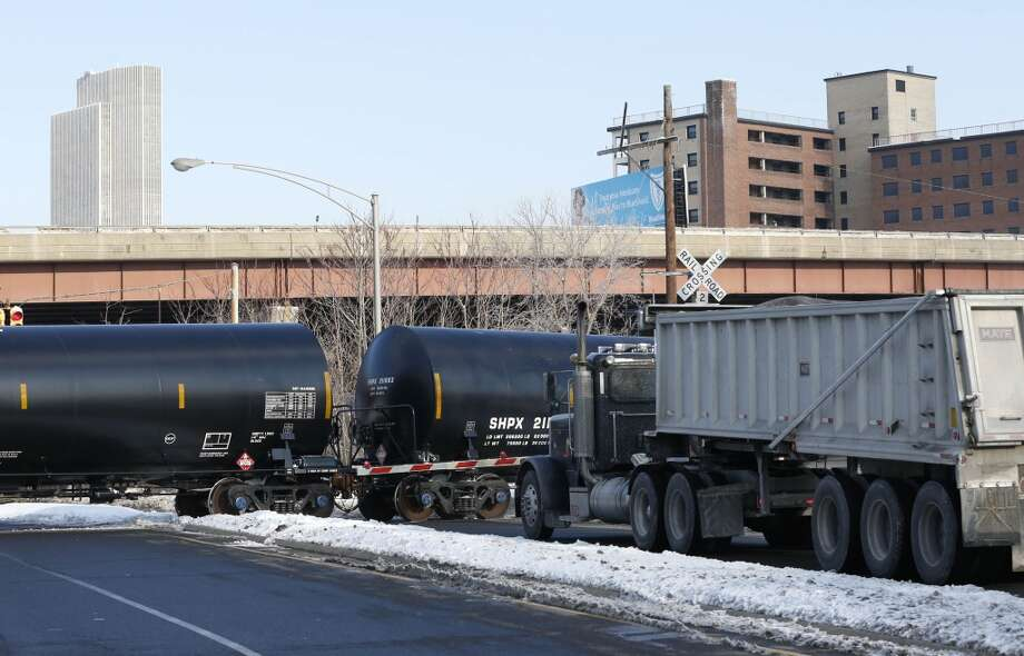 A truck waits as railroad oil tanker cars arrive at the Port of Albany on Friday, Feb. 7, 2014, in Albany, N.Y. The Port of Albany has become a hub for the U.S. oil business, taking shipments from North Dakota's Bakken Shale daily by mile-long trains and shipping it in tankers down the Hudson River to refineries. Opponents of a proposal to build boilers to liquefy heavy crude passing through Albany by rail are drawing attention to the capital's emergence as a major hub for the transport of oil that's widely considered risky from an environmental and safety standpoint.  (AP Photo/Mike Groll) Photo: Mike Groll, AP