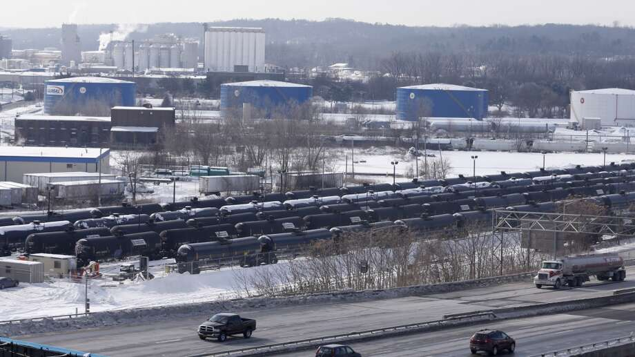 A view from a nearby apartment building shows vehicles driving along Interstate 787 past railroad oil tanker cars that are lined up at Global Partners at the Port of Albany on Friday, Feb. 7, 2014, in Albany, N.Y. The Port of Albany has become a hub for the U.S. oil business, taking shipments from North Dakota's Bakken Shale daily by mile-long trains and shipping it in tankers down the Hudson River to refineries. Opponents of a proposal to build boilers to liquefy heavy crude passing through Albany by rail are drawing attention to the capital's emergence as a major hub for the transport of oil that's widely considered risky from an environmental and safety standpoint.  (AP Photo/Mike Groll) Photo: Mike Groll, AP
