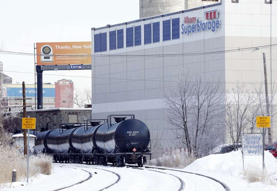 Railroad oil tanker cars are parked next to a storage facility near the Port of Albany on Friday, Feb. 7, 2014, in Albany, N.Y. The Port of Albany has become a hub for the U.S. oil business, taking shipments from North Dakota's Bakken Shale daily by mile-long trains and shipping it in tankers down the Hudson River to refineries. Opponents of a proposal to build boilers to liquefy heavy crude passing through Albany by rail are drawing attention to the capital's emergence as a major hub for the transport of oil that's widely considered risky from an environmental and safety standpoint.  (AP Photo/Mike Groll) Photo: Mike Groll, AP