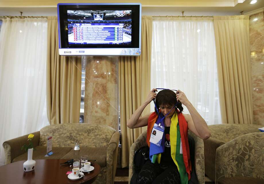 "Vladimir Luxuria, a former Communist lawmaker in the Italian parliament and prominent crusader for transgender rights, puts on her Olympic spectator pass after sitting for an interview, Monday, Feb. 17, 2014, in central Sochi, Russia, home of the 2014 Winter Olympics. Luxuria said she was detained by police at the Olympics after being stopped while carrying a rainbow flag that read in Russian: ""Gay is OK."" Police on Monday denied this happened. Photo: David Goldman, Associated Press"