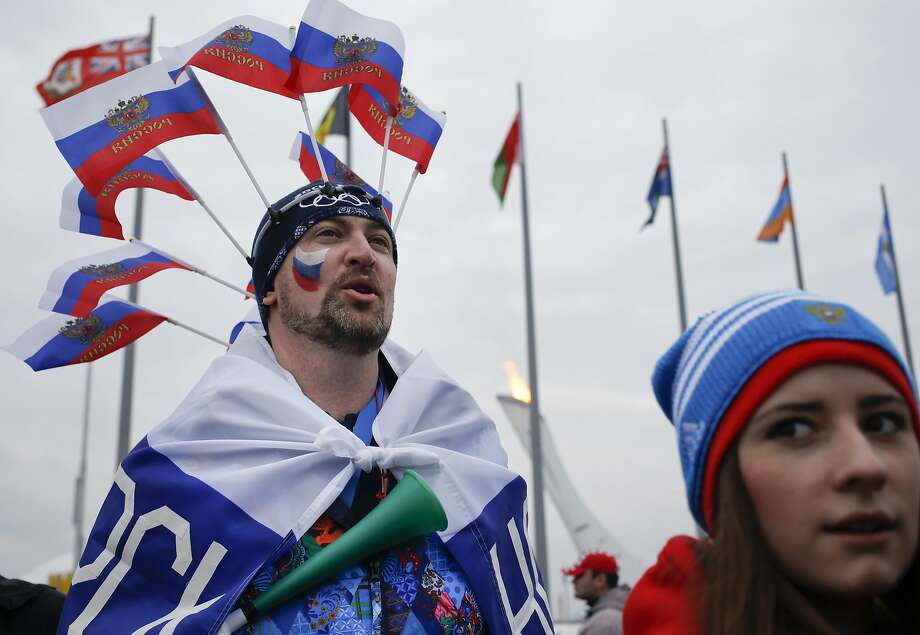 A fan wearing Russian flags passes the burning Olympic cauldron during the 2014 Winter Olympics, Monday, Feb. 17, 2014, in Sochi, Russia. Photo: Pavel Golovkin, Associated Press