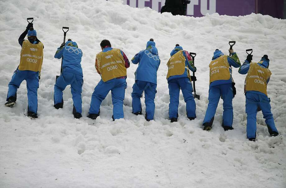 Crew members prepare the landing hill for athletes prior to the men's freestyle skiing aerials qualifying at the Rosa Khutor Extreme Park, at the Sochi 2014 Winter Olympics, Monday, Feb. 17, 2014, in Krasnaya Polyana, Russia. Photo: Charlie Riedel, Associated Press