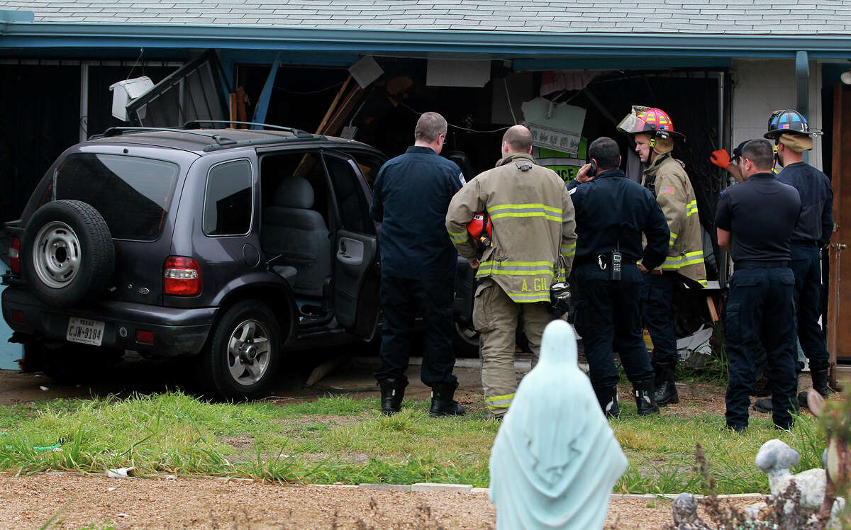 San Antonio firefighters and police prepare to extract a KIA SUV Monday morning February 17, 2014 that crashed through a fence and into the back of a house at Clearsprings and Perrin Beitel. SAPD patrolman T.J. Stout said the driver of the vehicle was a female in her twenties who lost control while turning through an intersection on a slick street. Stout said the driver was not seriously injured and nobody was in the house at the time of the accident.