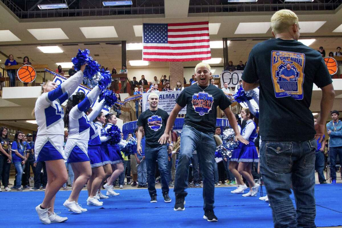 Senior Ajax Reyes runs through cheers during Lanier High School's pep rally for the men's basketball team, held Monday morning held in their cafeteria. The team dyed their hair blond as an ongoing basketball team tradition.