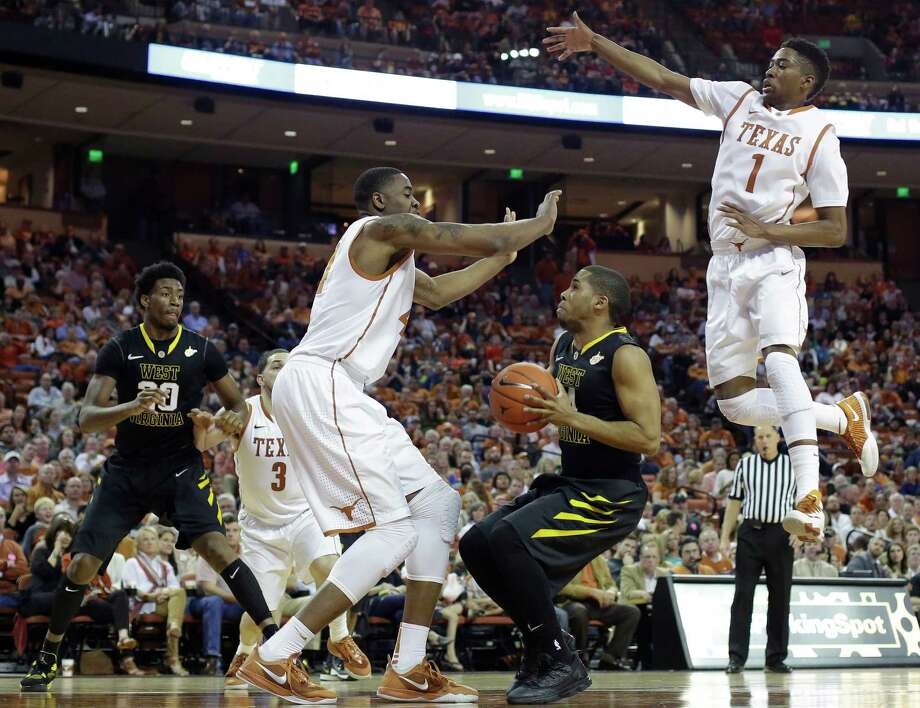 West Virginia's Gary Browne (14) is pressured by Texas' Prince Ibeh, left, and Isaiah Taylor, right, as he tries to shoot during the second half of an NCAA college basketball game, Saturday,  Feb. 15, 2014, in Austin, Texas. Texas won 88-71. (AP Photo/Eric Gay) Photo: Eric Gay, Associated Press / AP