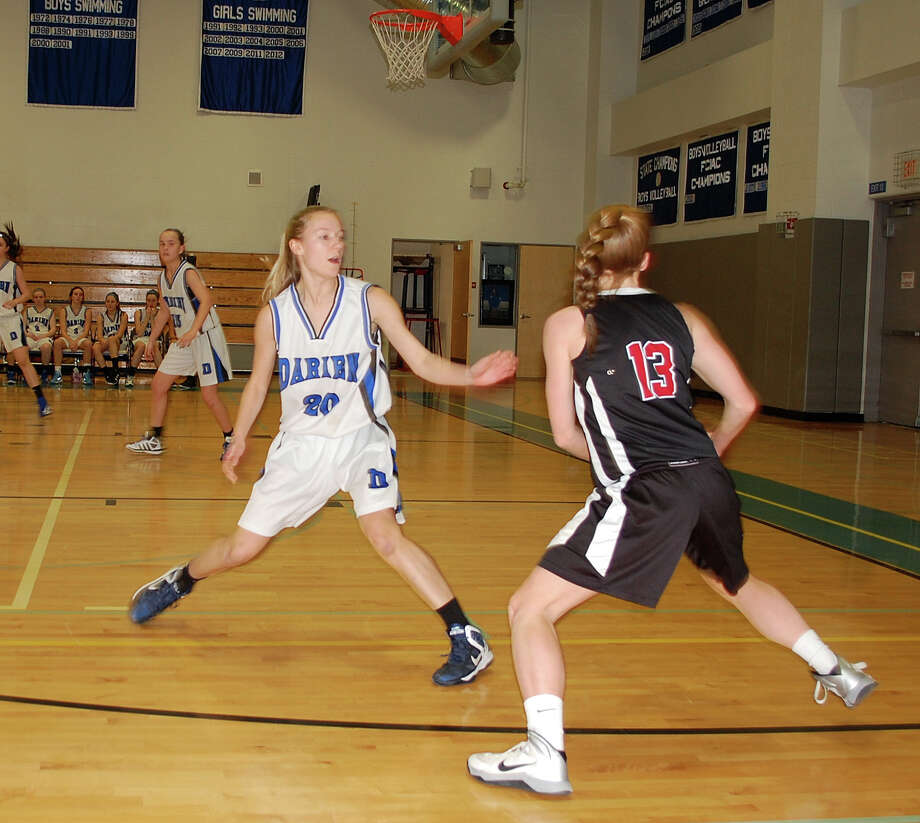 Darien High School's Kelly Karczewski (#20) boxes out New Canaan's Elisabeth Miller (#13) in girls basketball contest in Darien, Conn. on Saturday, Feb. 22, 2014. Photo: Dave Crandall / Darien News freelance