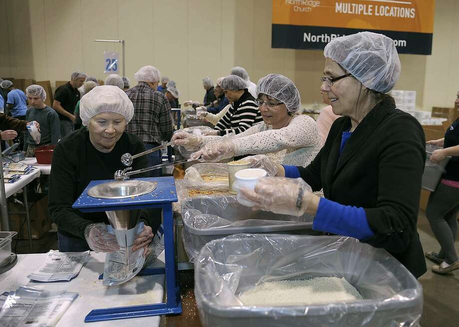 Members of NorthRidge Church near Detroit put rice into meals for malnourished children Friday. Photo: Clarence Tabb Jr, Associated Press