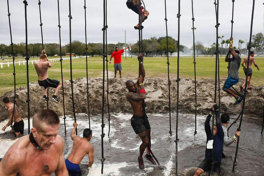 Testing their mettle: Competitors in the Special Ops Spartan Sprint climb up and down ropes over a mud pit at Raymond James Stadium in Tampa, Fla. The course's obstacles included crawling under barbed wire. Photo: Eve Edelheit, Associated Press