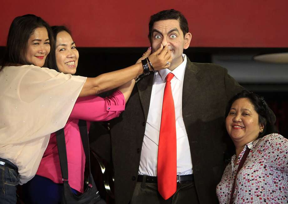 Bean stalkers: Tourists abuse the wax figure of Mr. Bean at the Red Carpet Wax Museum in Shah Alam, Malaysia. Photo: Lai Seng Sin, Associated Press