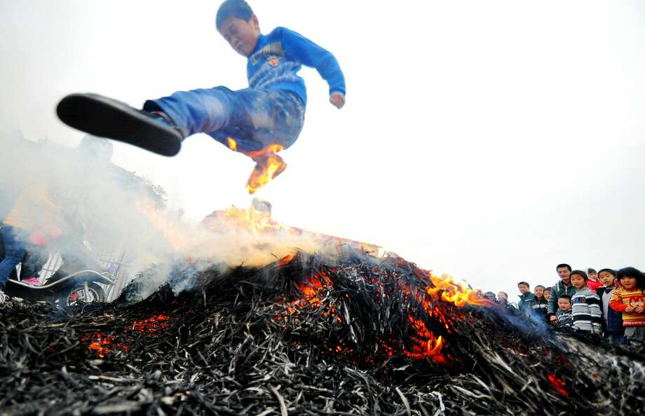 Boys to men, Chinese-style: A boy leaps over a bonfire at a village in Puning, southern China's Guangdong province, during a ritual marking his coming of age. Photo: Stringer, AFP/Getty Images