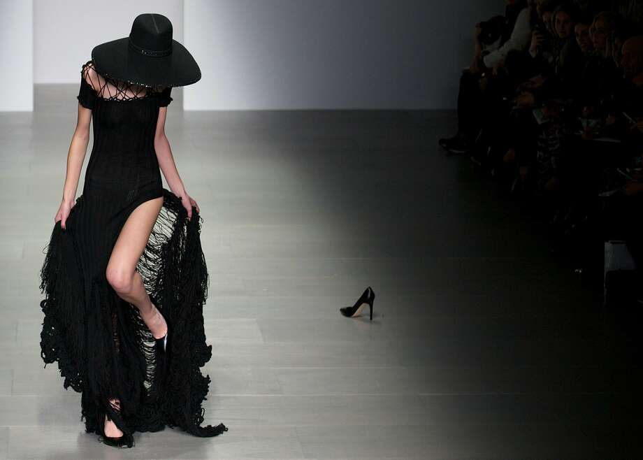 Stiletto-catching styles: A model gets her heel caught in her dress at the Sister by Sibling collection for London Fashion Week. Another model who suffered the same mishap left her shoe on the catwalk. Photo: Andrew Cowie, AFP/Getty Images