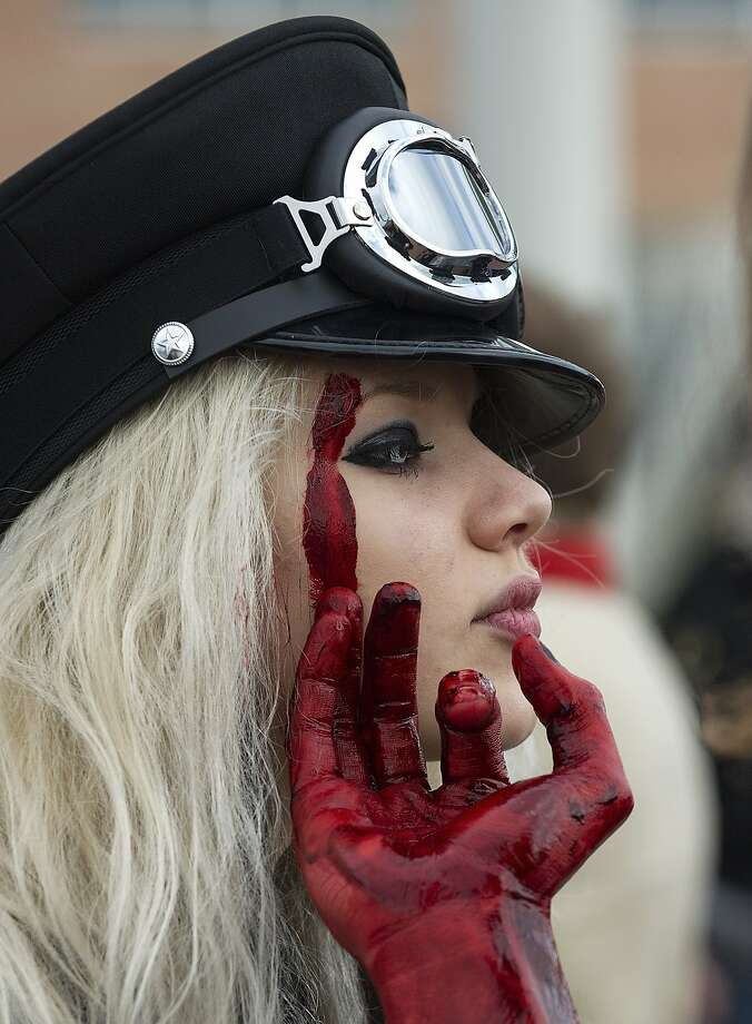 "You should have that looked at:A bloody finger grazes a ""zombie hunter's"" face at the Carnival of Venice, Italy. Photo: Marco Secchi, Getty Images"