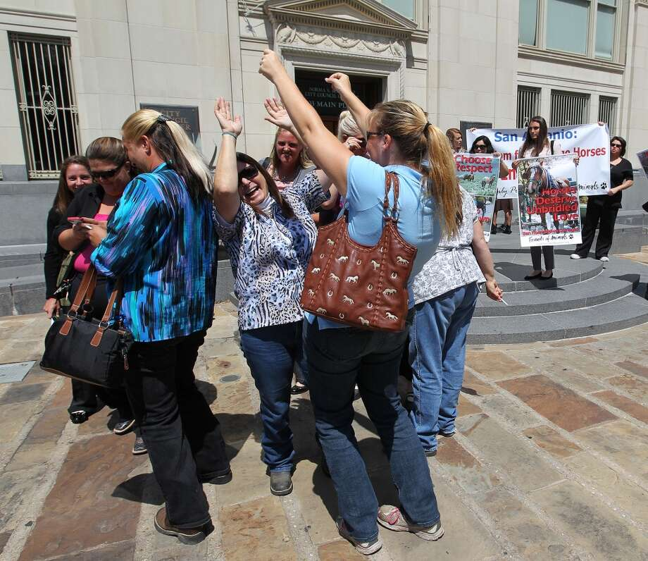 Horse carriage drivers celebrate after the San Antonio City Council votes to approve new regulations for the horse carriage industry, Thursday, August 1, 2013. In back are animal rights activist that wanted the city to ban the practice. Photo: San Antonio Express-News