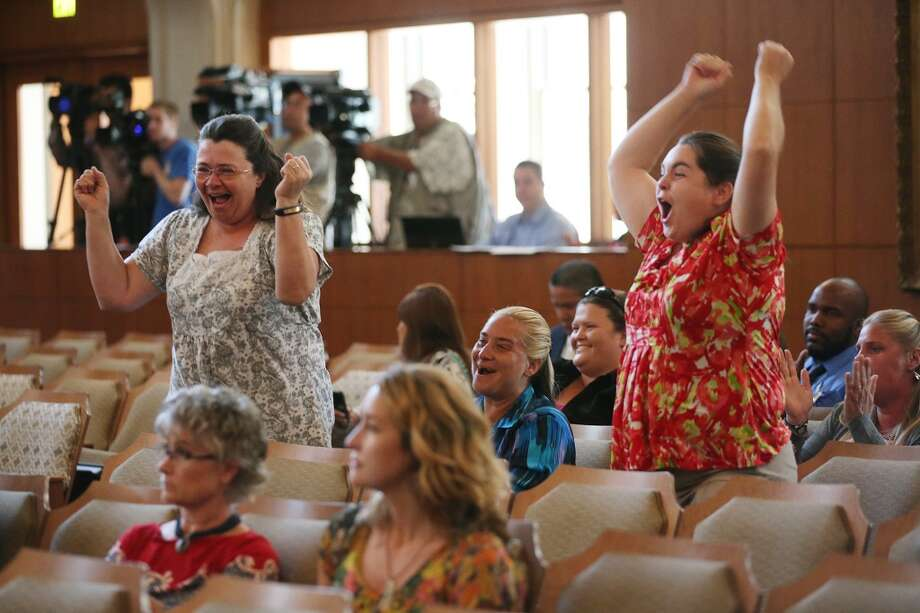 Stephanie McMeans, standing left, and Emily Benson, standing right, celebrate after the San Antonio City Council votes to approve new regulations for the horse carriage industry, Thursday, August 1, 2013. In back are animal rights activist that wanted the city to ban the practice. Photo: San Antonio Express-News