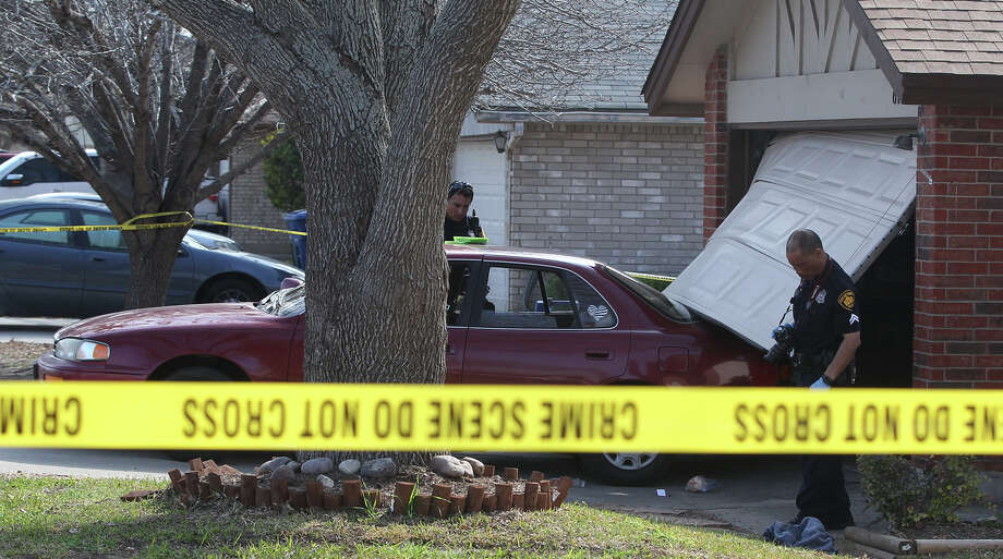 San Antonio police investigate the scene of a shooting that took place Monday February 17, 2014 at a northwest side home at 615 River Village. A homeownwer shot at 3 burglars who were inside the garage and attempted to drive a car through the garage door. Two of the burglars were shot and transported by EMS. One burglar is in custody according to San Antonio police sergeant James Cline. Photo: JOHN DAVENPORT, SAN ANTONIO EXPRESS-NEWS / ©San Antonio Express-News/Photo may be sold to the public
