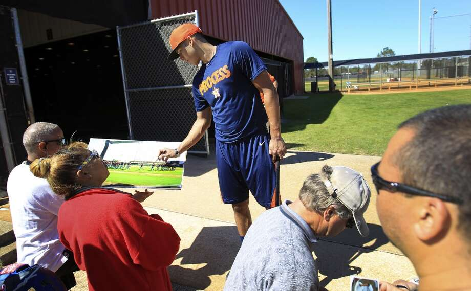 Carlos Correa signs autographs after workouts for early-arriving position players on Monday. Photo: Karen Warren, Houston Chronicle