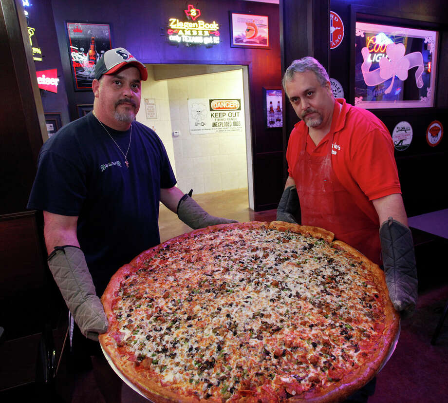 Brothers, from the left, Art and Brian Lujan show off one of the famous 42-inch pizzas. 'Man vs Food' host Adam Richman visited the establishment. Photo: J. Michael Short, SPECIAL TO THE EXPRESS-NEWS / THE SAN ANTONIO EXPRESS-NEWS
