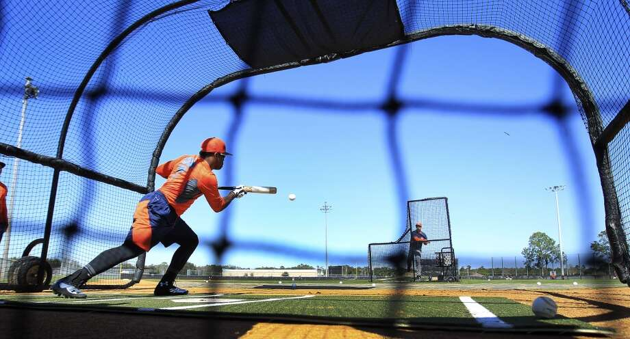 Delino DeShields bunts a ball in the batting cages during workouts for early-arriving position players. Photo: Karen Warren, Houston Chronicle