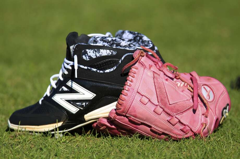 Jerome Williams' pink glove sits in the grass as he and other players stretch during workouts for pitchers and catchers. Williams uses the glove in honor of his mother, Deborah, who died of breast cancer in 2001. Photo: Karen Warren, Houston Chronicle