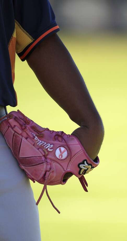 Jerome Williams with his pink glove as he prepared to pitch during workouts for pitchers and catchers. Williams uses the glove in honor of his mother, Deborah, who died of breast cancer in 2001. Photo: Karen Warren, Houston Chronicle