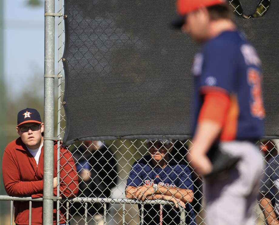 An Astros fan watches pitchers throw during workouts for pitchers and catchers on Monday. Photo: Karen Warren, Houston Chronicle