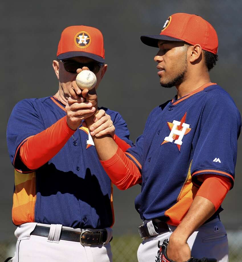 Astros spring training coach and pitching coach for the Oklahoma City Redhawks, Steve Webber, left, shows Jorge De Leon how he should be holding the ball during workouts. Photo: Karen Warren, Houston Chronicle